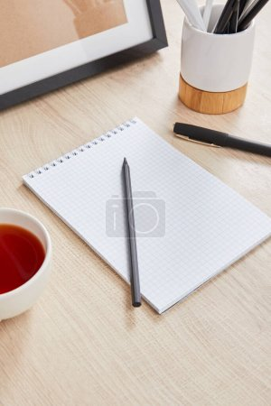 cup of tea and blank notebook with pencil and pen on wooden surface