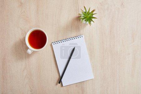 Foto de Vista superior de la planta verde, taza de té y cuaderno en blanco con lápiz en la superficie de madera - Imagen libre de derechos