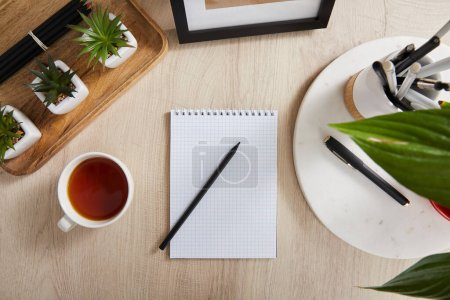 Photo for Top view of green plants, cup of tea and blank notebook with pencils and pens on wooden surface - Royalty Free Image