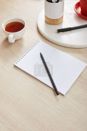 Photo for Cup of tea and blank notebook with pencil and pen on wooden surface - Royalty Free Image