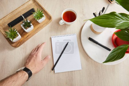 Photo for Top view of male hand near green plants, cup of tea and blank notebook with pencils and pens on wooden surface - Royalty Free Image