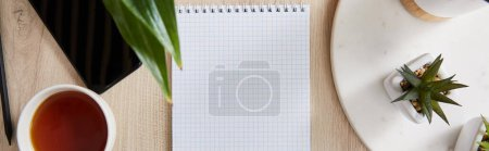 top view of green plants, cup of tea and blank notebook with pencil and smartphone on wooden surface, panoramic shot