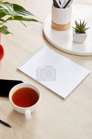 Photo for Green plants, cup of tea and blank notebook near smartphone on wooden surface - Royalty Free Image