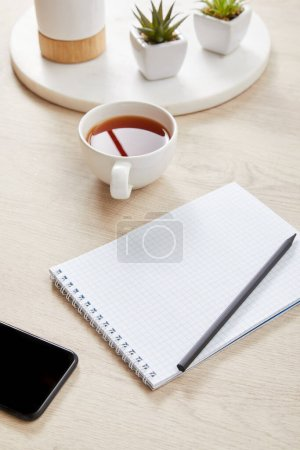 Photo for Green plants, cup of tea and blank notebook with pencil near smartphone on wooden surface - Royalty Free Image