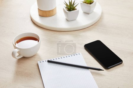green plants, cup of tea and blank notebook with pencil near smartphone on wooden surface