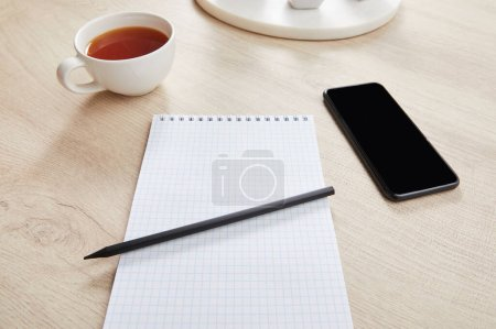cup of tea and blank notebook with pencil near smartphone on wooden surface