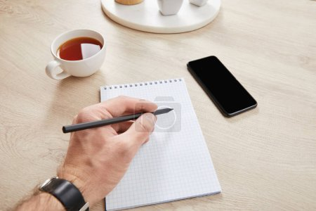 cropped view of man writing in notebook near cup of tea and smartphone on wooden surface