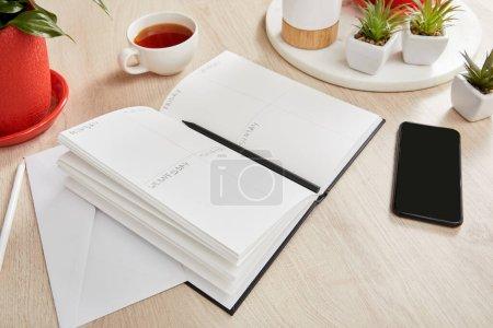 Foto de Plantas verdes, taza de té, sobre, cuaderno con lápices cerca de smartphone en superficie de madera. - Imagen libre de derechos