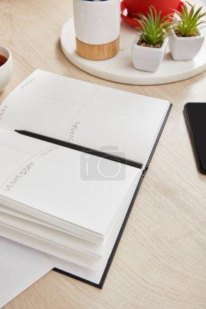 Foto de Plantas verdes, cuaderno con lápiz en superficie de madera. - Imagen libre de derechos