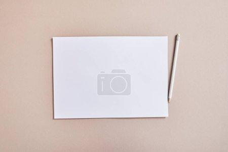 Photo pour Vue du dessus du papier blanc vierge avec crayon sur la surface beige - image libre de droit