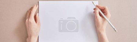 Photo pour Vue recadrée d'une femme écrivant sur papier avec crayon sur surface beige, prise de vue panoramique - image libre de droit