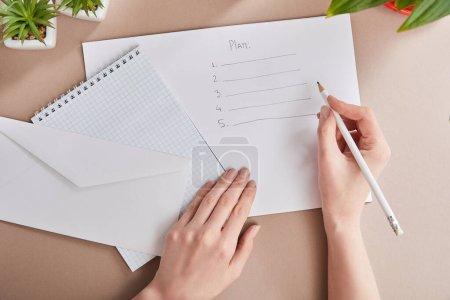 Photo pour Vue recadrée du plan d'écriture femme sur papier près des plantes vertes, enveloppe, carnet vierge sur surface beige - image libre de droit