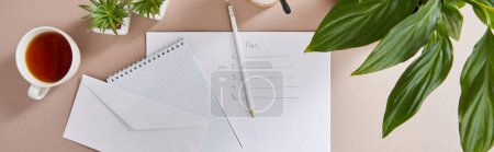 Photo for Top view of green plants, cup of tea, envelope, blank notebook, pencil and paper with plan lettering on beige surface, panoramic shot - Royalty Free Image