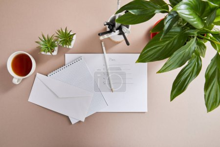 Photo for Top view of green plants, cup of tea, envelope, blank notebook, pencils and pens and paper with plan lettering on beige surface - Royalty Free Image