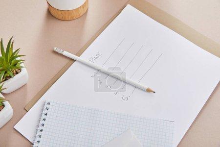 Foto de Plantas verdes, cuaderno en blanco, lápiz, papel con hojas planas sobre superficies beige. - Imagen libre de derechos