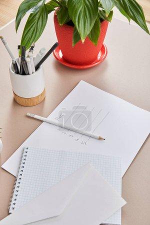 Photo pour Plante verte, enveloppe, carnet vierge, crayons et stylos et papier avec lettrage plan sur surface beige - image libre de droit