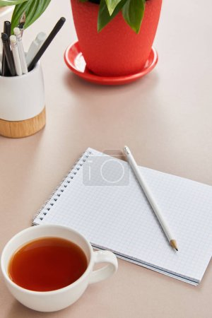 Photo for Green plant, cup of tea, blank notebook with pencils on beige surface - Royalty Free Image