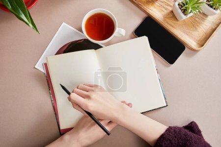 Photo pour Vue recadrée d'une femme écrivant dans un cahier près de plantes vertes sur une planche de bois, tasse de thé, smartphone sur une surface beige - image libre de droit