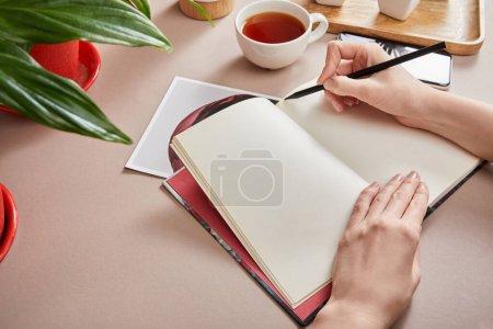 Photo pour Vue recadrée de femme écrivant dans le planificateur près de la plante verte, tasse de thé, smartphone sur la surface beige - image libre de droit