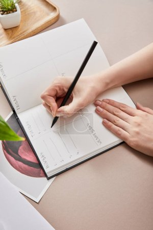 Photo for Cropped view of woman writing in planner on beige surface - Royalty Free Image