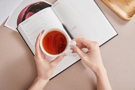 Photo for Top view of female hands with cup of tea near planner with pencil on beige surface - Royalty Free Image