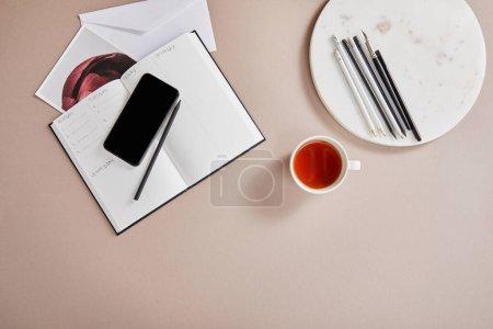 Photo pour Vue du dessus de tasse de thé, enveloppe, planificateur, carte, smartphone près du cercle avec crayons sur la surface beige - image libre de droit