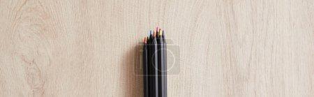 Photo pour Vue de dessus des crayons de couleur noire sur la surface beige bois, vue panoramique - image libre de droit