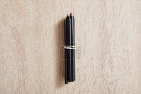 Draufsicht auf schwarze Buntstifte auf hölzerner beiger Oberfläche