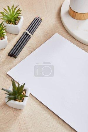 Foto de Plantas verdes, lápices coloreados cerca de papel blanco y tablero de piedra con soporte en superficie de madera. - Imagen libre de derechos