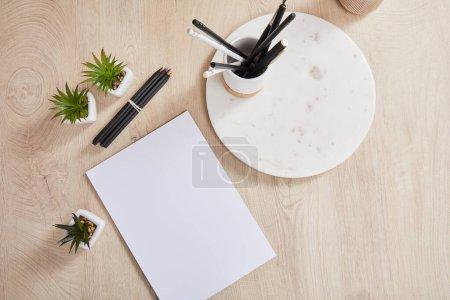 Foto de Vista superior de plantas verdes, lápices coloreados cerca de papel blanco y tablero de piedra con soporte en superficie de madera. - Imagen libre de derechos