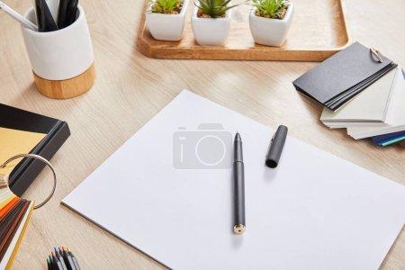 Foto de Plantas verdes, lápices de colores, paleta de colores y papel blanco con pluma en superficie de madera. - Imagen libre de derechos