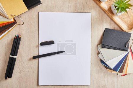 Foto de Vista superior de plantas verdes, lápices de colores, paleta de colores y papel blanco con pluma en superficie de madera. - Imagen libre de derechos