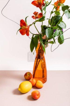 Photo pour Composition florale avec des roses et Alstroemeria rouge en fils dans un vase orange près de citron et abricots isolés sur blanc - image libre de droit