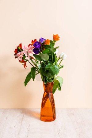 Photo pour Composition florale avec bouquet en vase orange sur fond beige - image libre de droit