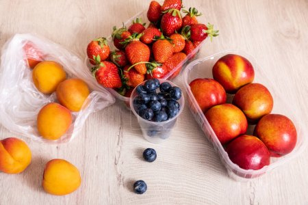 Photo for Fruit composition with blueberries, strawberries, nectarines and peaches in plastic containers on wooden surface - Royalty Free Image