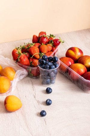 Photo for Fruit composition with blueberries, strawberries, nectarines and peaches in plastic containers on wooden surface isolated on beige - Royalty Free Image