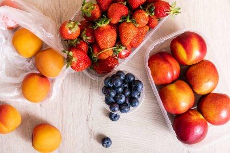 Photo pour Vue de dessus de la composition des fruits avec des bleuets, des fraises, des nectarines et des pêches dans des récipients en plastique sur la surface en bois - image libre de droit