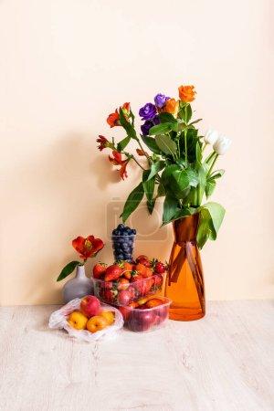 Foto de Composición floral y frutal con bouquet en jarrón y frutas de verano en superficie de madera sobre fondo beige. - Imagen libre de derechos