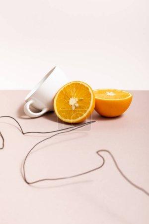 Fruchtzusammensetzung mit Draht, orange, Tasse isoliert auf beige