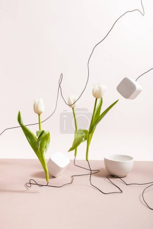 Photo for Creative floral composition with tulips on wires, cup and square cubes isolated on beige - Royalty Free Image