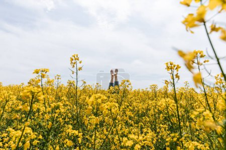 Photo for Cropped view of barefoot woman near yellow flowers in field against sky - Royalty Free Image