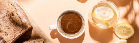 Photo pour Vue du dessus de la tasse à café, verre d'eau et pain pour le petit déjeuner sur table beige, image horizontale - image libre de droit