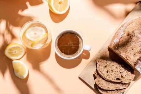 Photo pour Vue du dessus de la tasse à café, verre d'eau au citron et pain pour le petit déjeuner sur table beige - image libre de droit