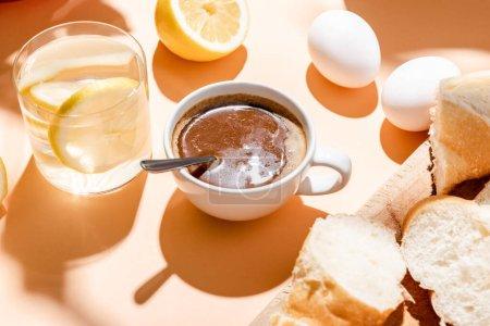 Photo pour Café, oeufs, baguette et verre d'eau pour le petit déjeuner sur table beige - image libre de droit