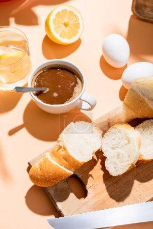Photo pour Tasse à café avec cuillère à café, oeufs, baguette et verre d'eau au citron pour le petit déjeuner sur table beige - image libre de droit