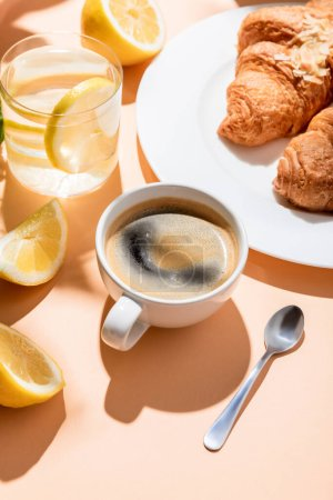 Photo for Coffee cup with teaspoon, croissants and glass of water with lemon for breakfast on beige table - Royalty Free Image