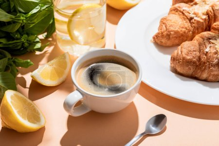 Photo for Coffee, croissants and glass of water with lemon for breakfast on beige table - Royalty Free Image