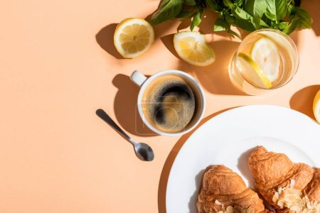 Photo for Top view of coffee cup and croissants for breakfast on beige table - Royalty Free Image
