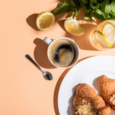 Photo for Top view of coffee cup, greenery, lemons and croissants for breakfast on beige table - Royalty Free Image