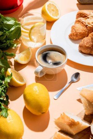 coffee, croissants, water with lemon for breakfast on beige table
